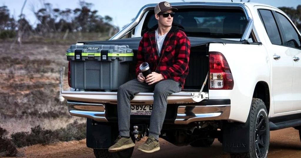 Man sitting in the back of a pickup near a Pelican hard cooler