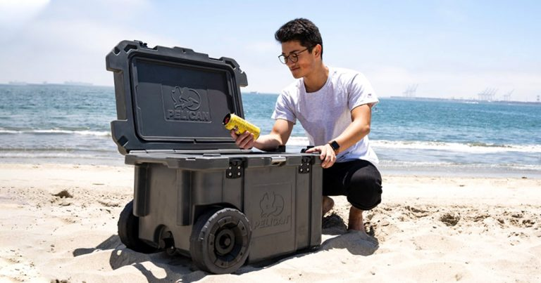 Man picking a beer from a Pelican wheeled hard cooler on the beach