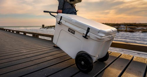 Man carring a YETI wheeled cooler on a bridge