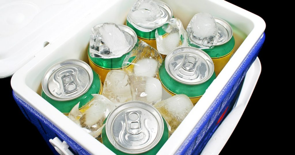 Icy cold cans of drink in a plastic cooler