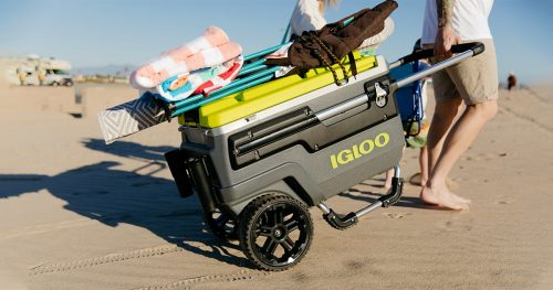 Man carrying igloo wheeled cooler on the beach