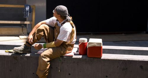 Worker takes a lunch break in the midday sun near a cooler box