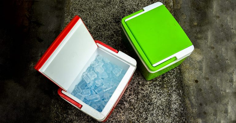 Top view of picnic cooler box with and ice cube on the ground for camping during summer vacation time
