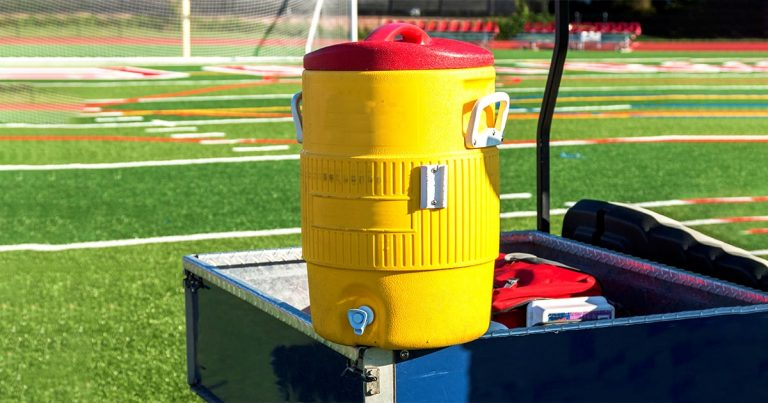 A yellow water cooler sits on a blue golf cart during a soccer game