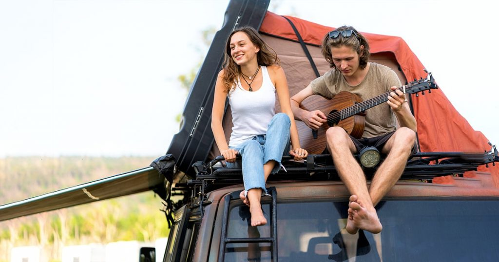 Couple sitting on the camp car roof top, playing guitar and singing together