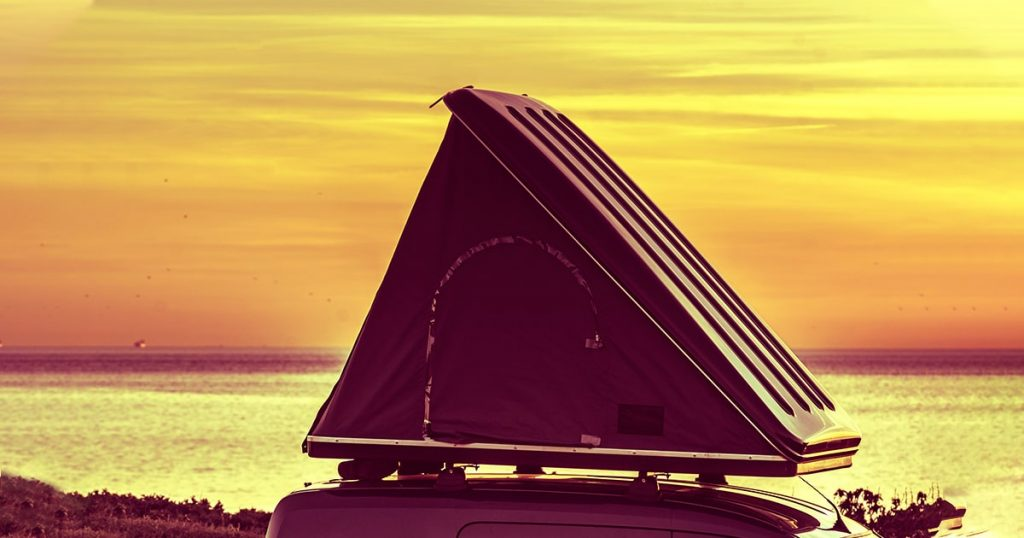 Car with roof top tent camping on mediterranean coast at sunrise