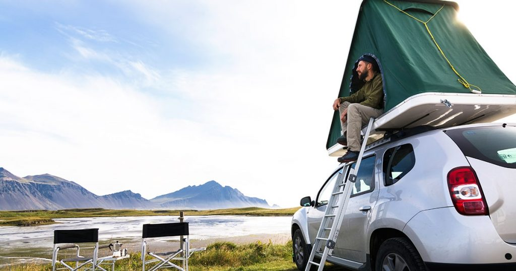 man sitting in a roof top tent mounted on off road car.