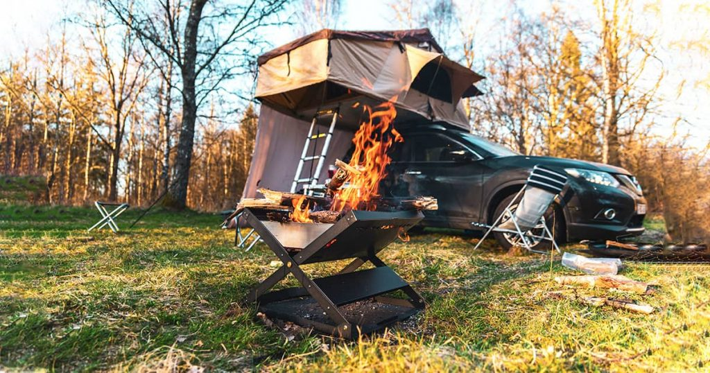 A car on a campsite with a roof tent and a mobile fire pit