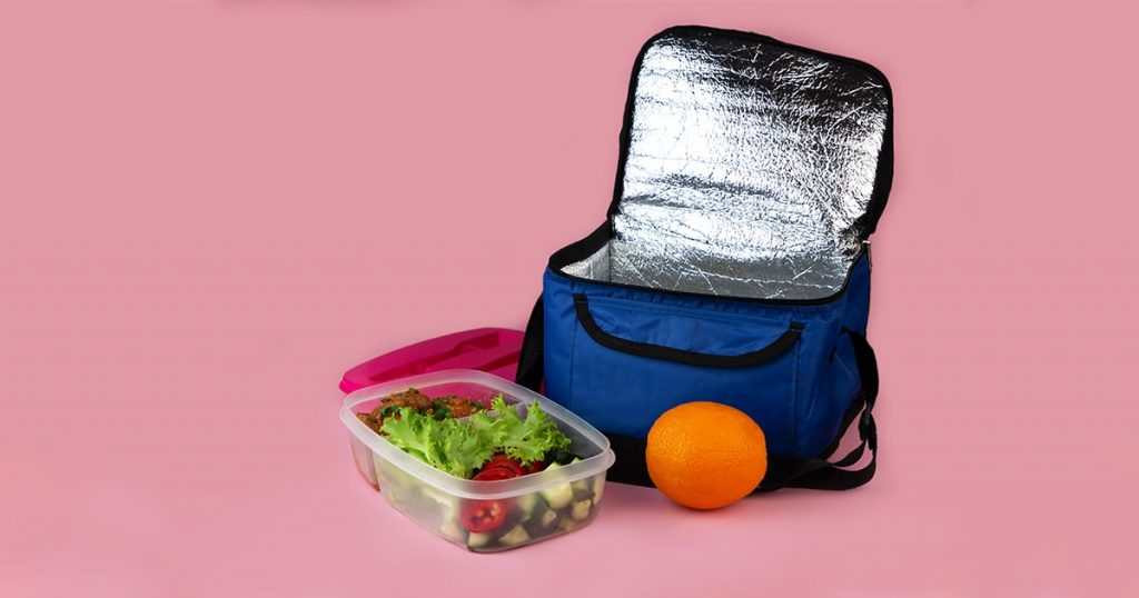 Thermal bag and container with salad, meat and orange.