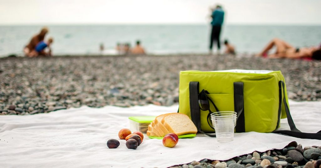 A picnic bag and food on the coverlet