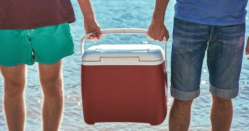 people walking by the beach to the sea while two men carrying plastic cooler