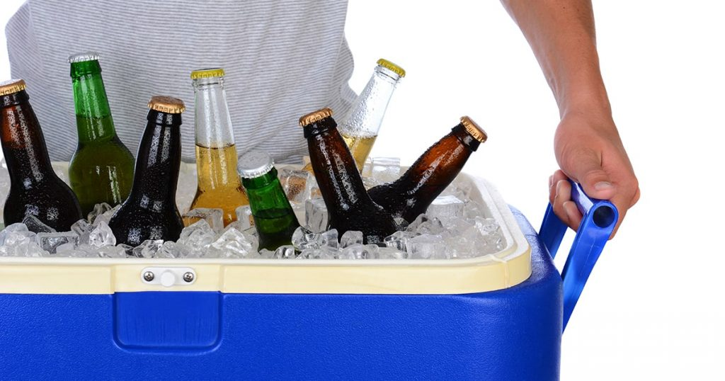 Closeup of a fit young man carrying an ice chest full of beer