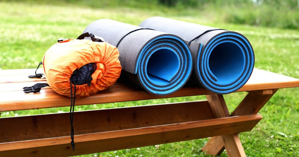 Sleeping pad and tent lie on a wooden bench.