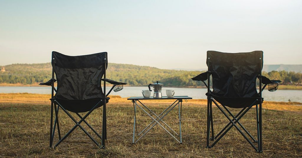 Outdoor two empty chairs with picnic table and moka pot coffee for Camping.