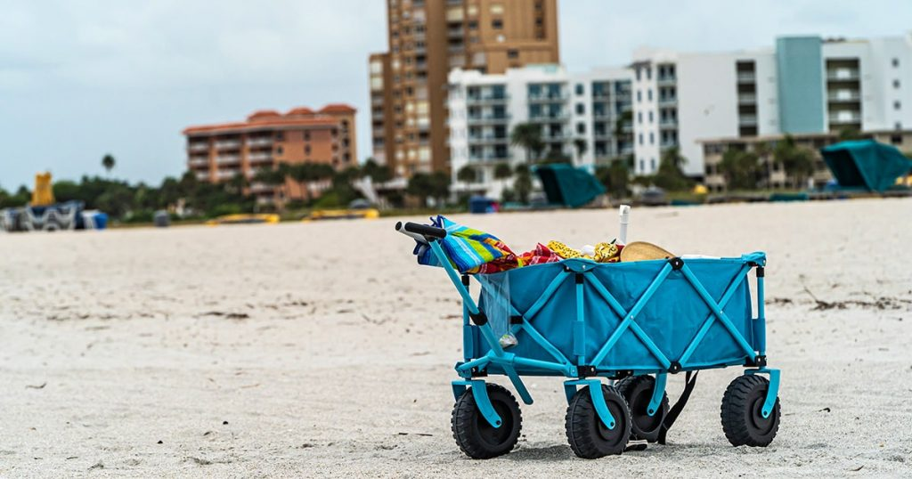 blue cart on sandy beach against hotels and dark clouds in background. High quality photo