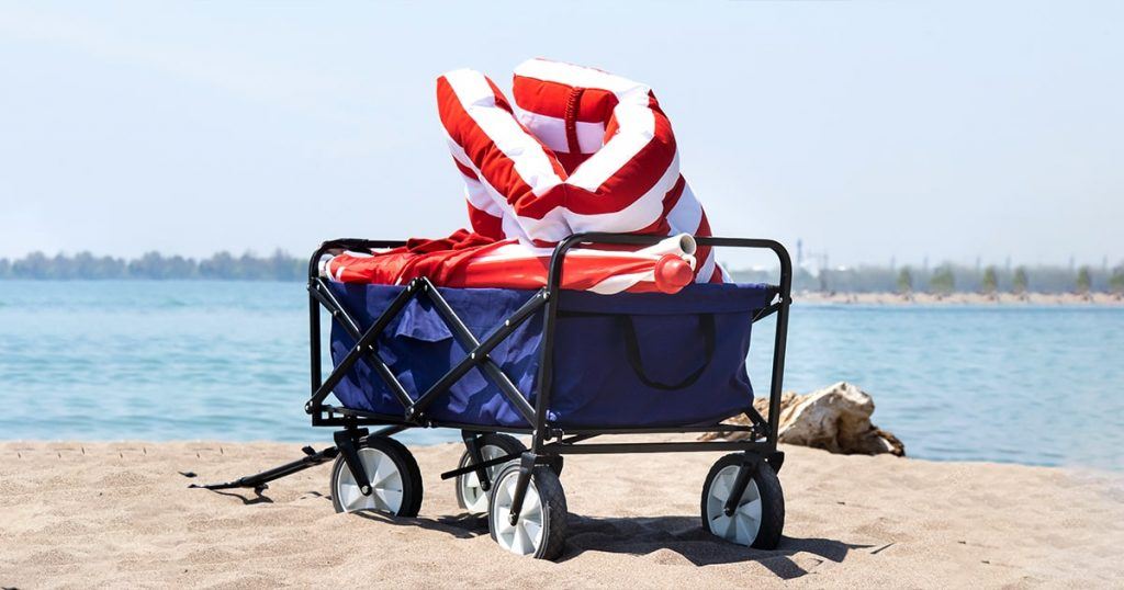a folding beach wagon on the sand filled with red cushions and an umbrella