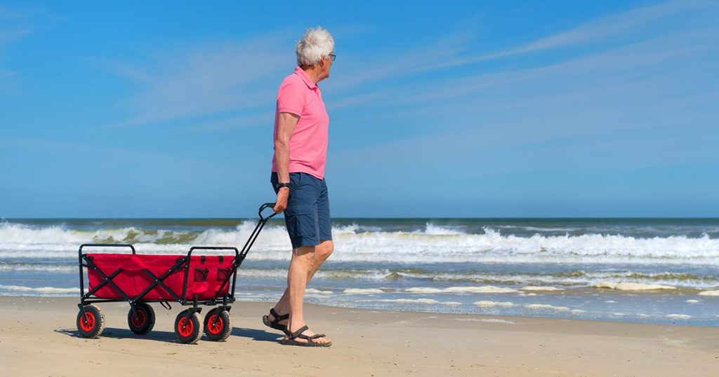 Senior man walking with empty red cart at the beach