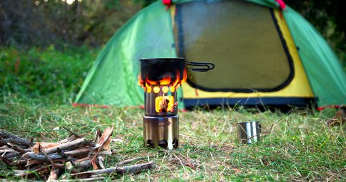 food is cooked on a camping wood stove. green tent on the grass at the background