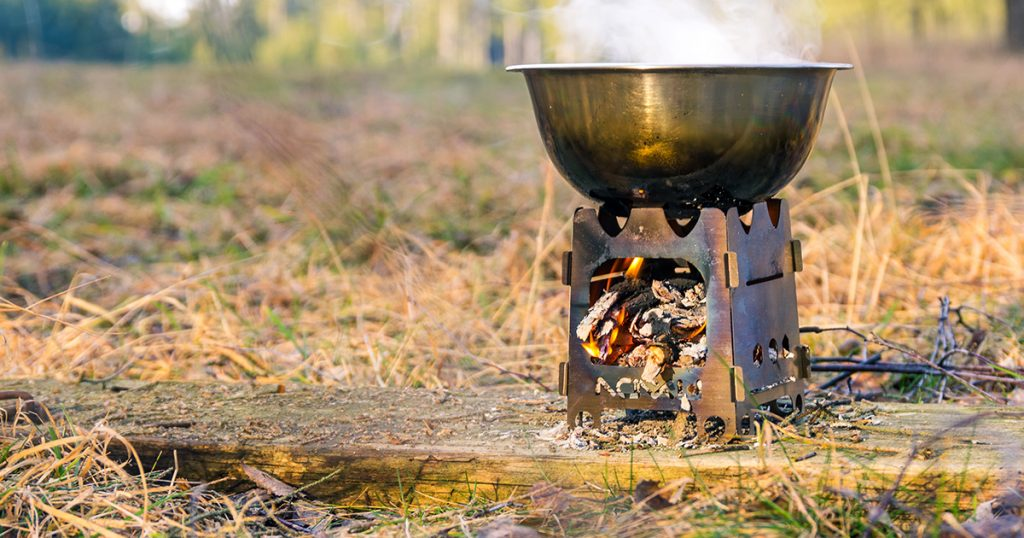 Outdoors cooking on small portable wood stove.