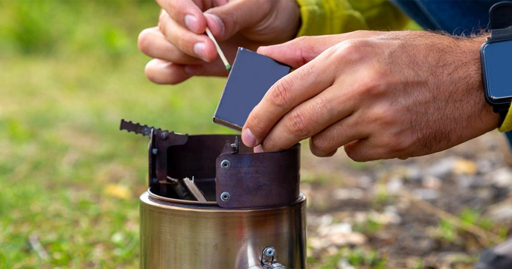Tourist equipment and tools: camping stove burning out. Igniting with matches.