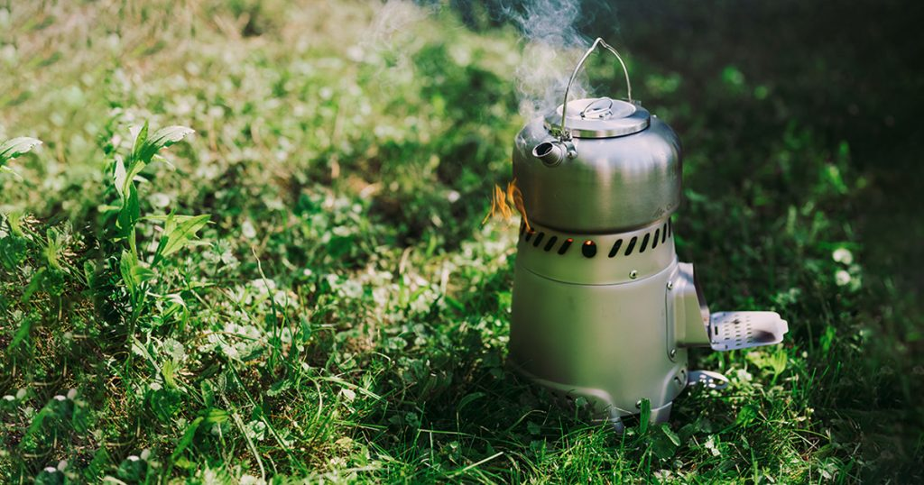 Outdoor cooking concept. Small, portable stove on woods with kettle on