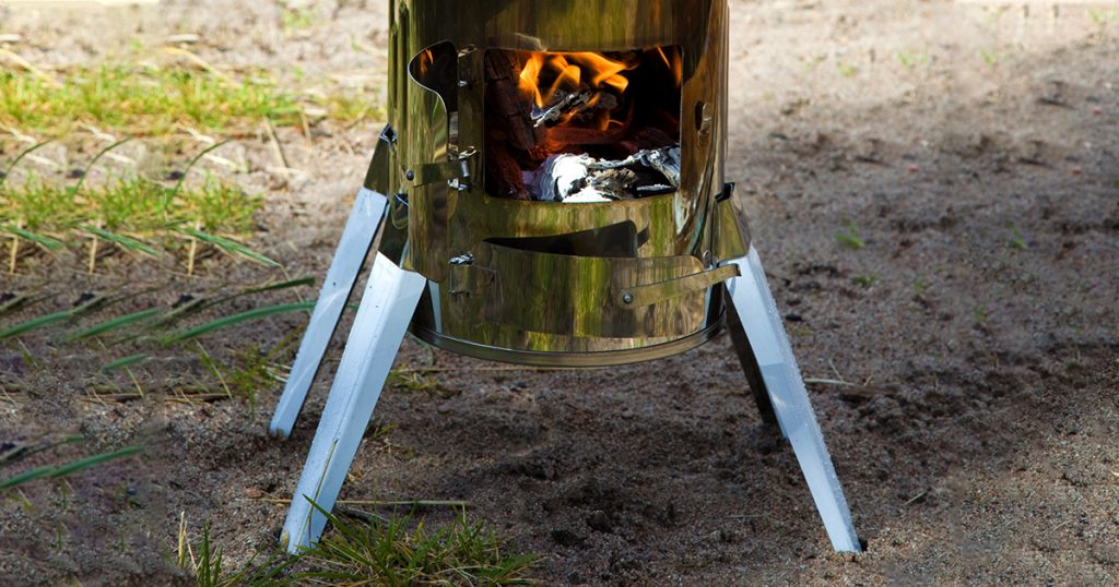 Modular wood stove for the tourist with an open door where the fire is visible