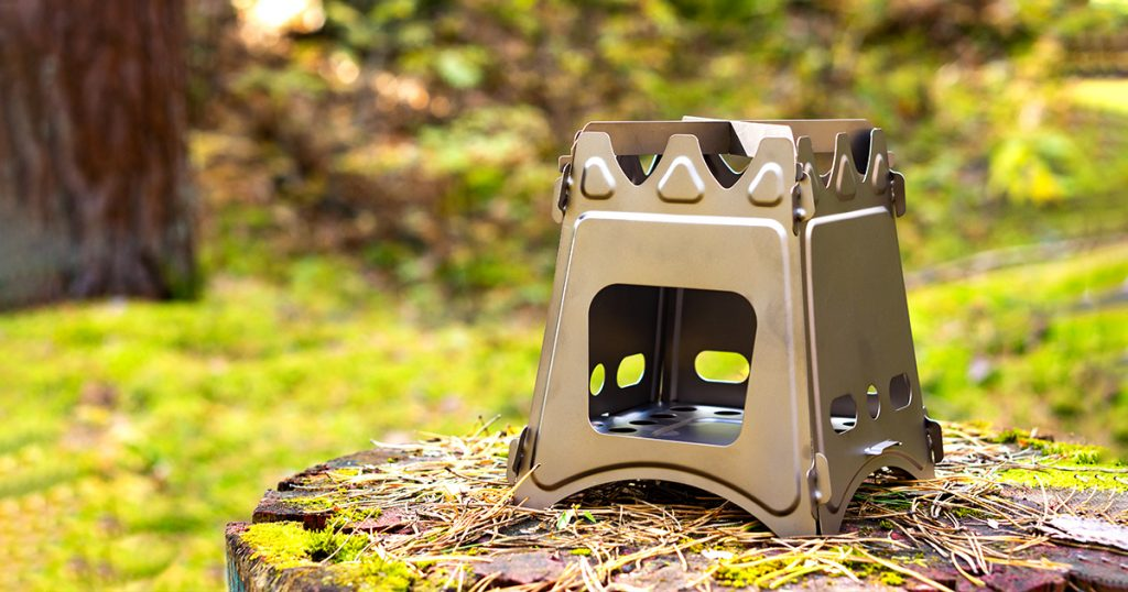 Folding wood stove designed for cooking outdoors using twigs as fuel on nature background