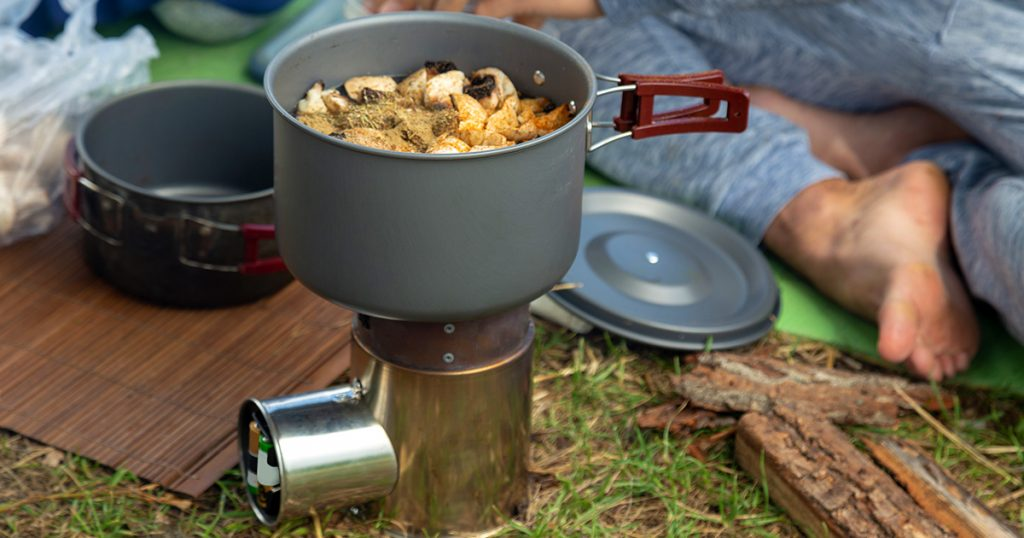 Camping food making. Pasta on pan on tourist fire stove