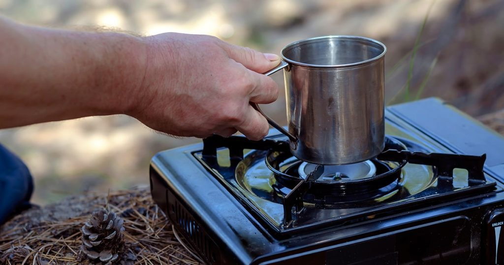 Herbal tea in a metal mug in hand over a portable gas stove.