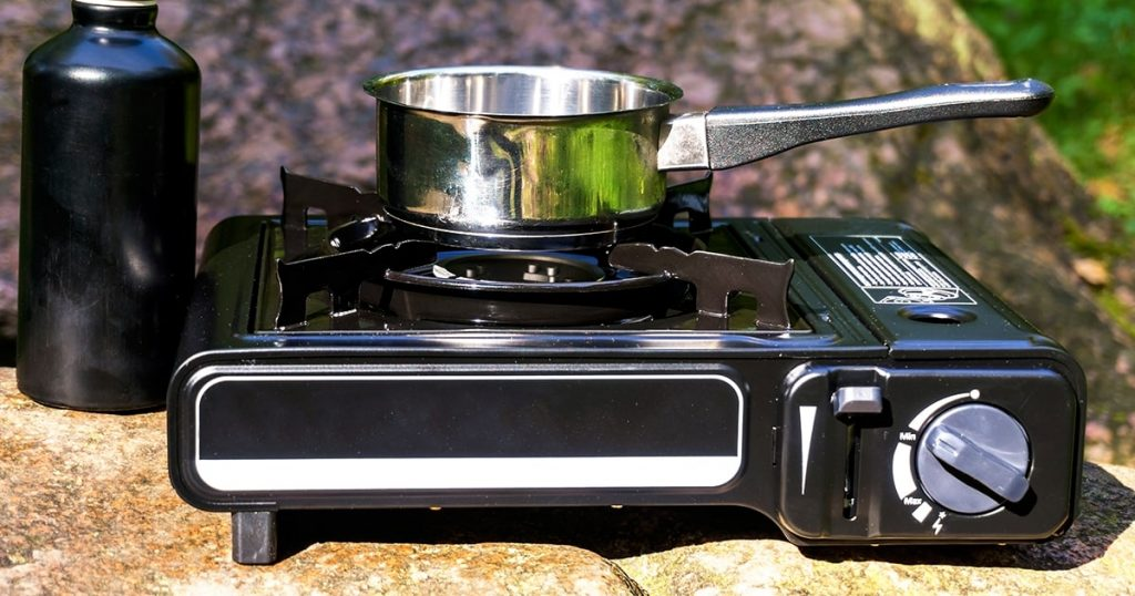 Portable tourist stove with pot and water bottle. Cooking in the camp.
