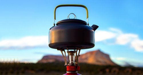 Boiling water on portable gas camping stove with a kettle to make coffee or tea.