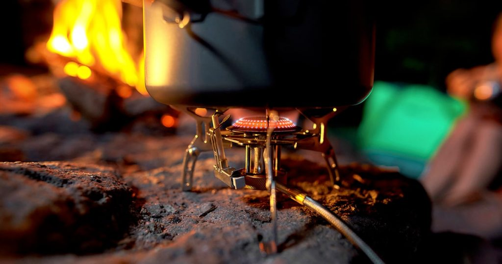 Closeup of foldable camping gas fire system with gas and a pot for fast heating