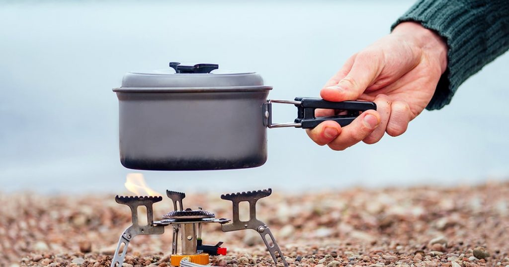 The pan with the porridge stands on the gas burner (Camping Stove)