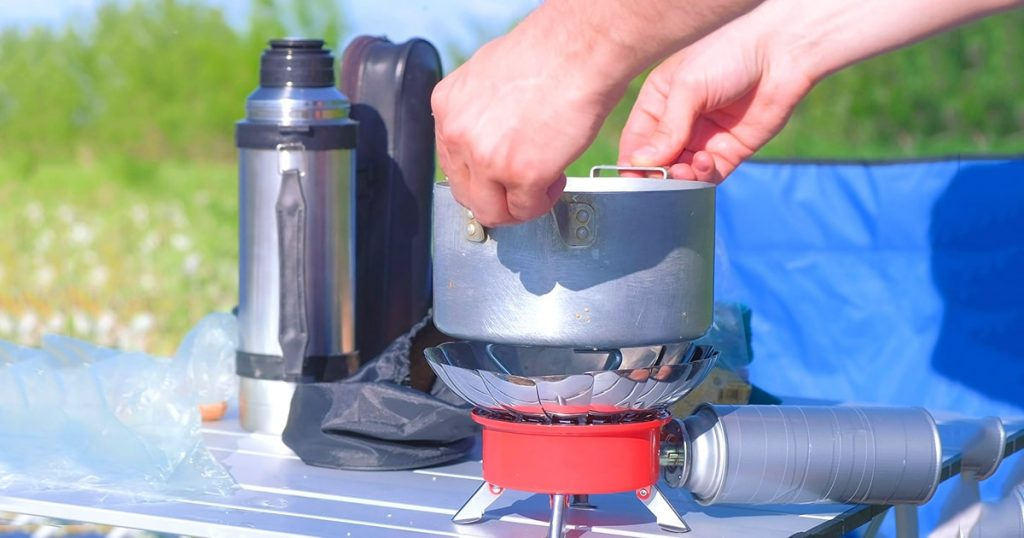 Man is cooking food using small gas burner in camping on nature, hands closeup