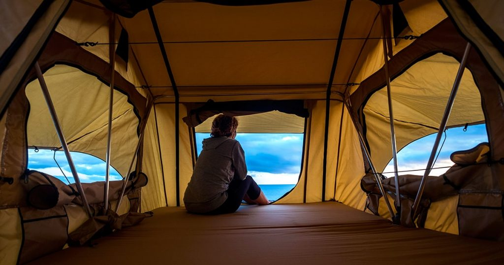 middle age woman feeling the nature outdoor in a roof tent on the car