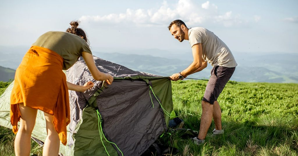 Young couple setting up the tent on the green meadow