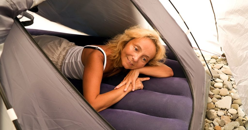 woman in a tent on an inflatable mattress