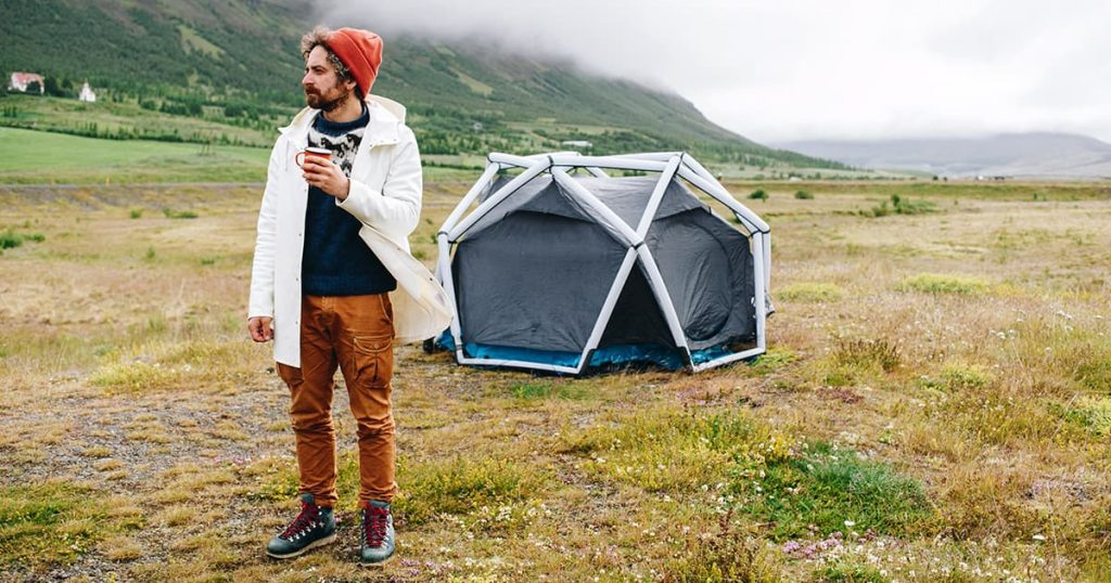 man in outdoor outfit and wool knit sweater who stands next to futuristic inflatable camping tent