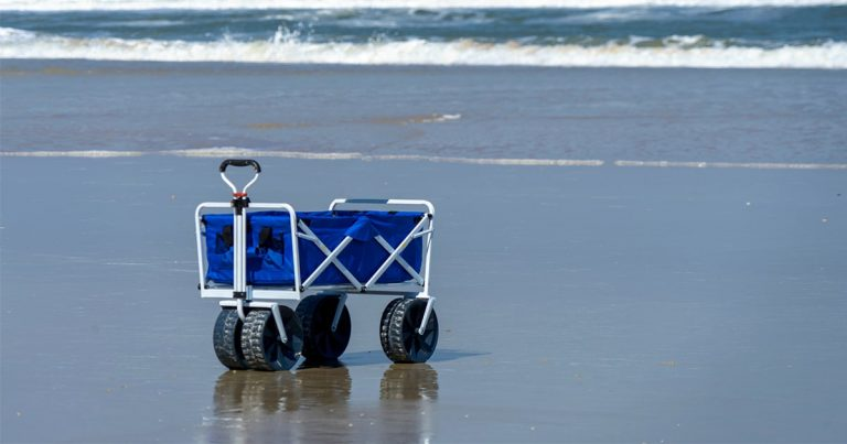 blue wagon on the beach with the waves rolling in