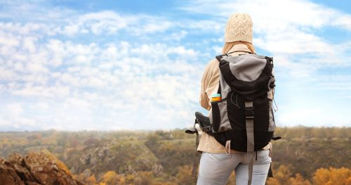Traveler with backpack enjoying beautiful view on sunny day. Autumn vacation