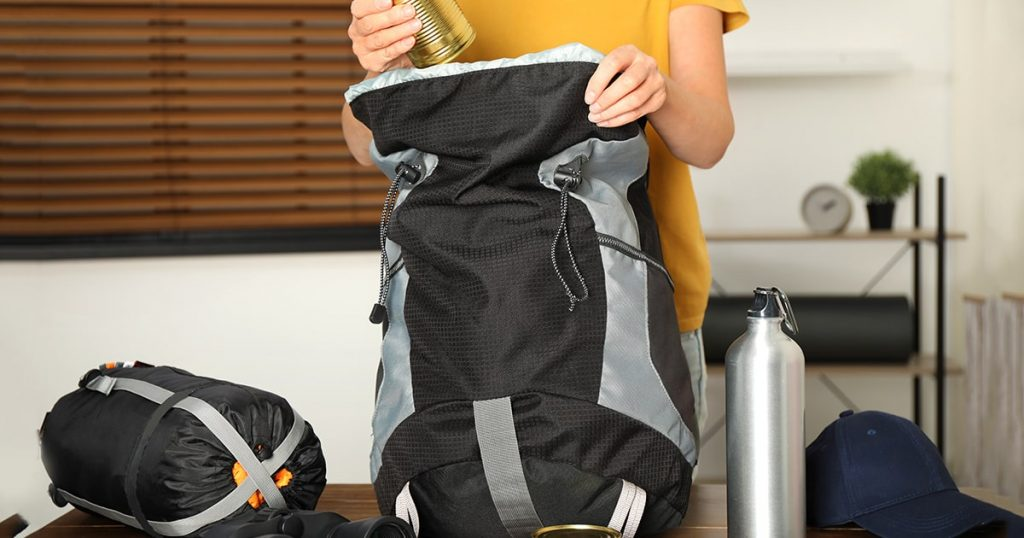 Woman packing different camping equipment into backpack at home, closeup