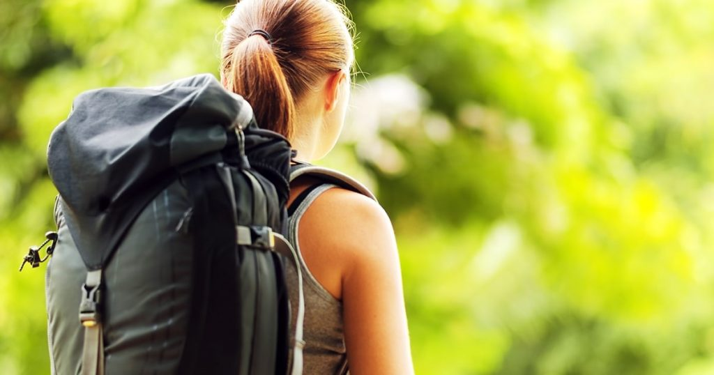 Young woman with backpack in a woods.