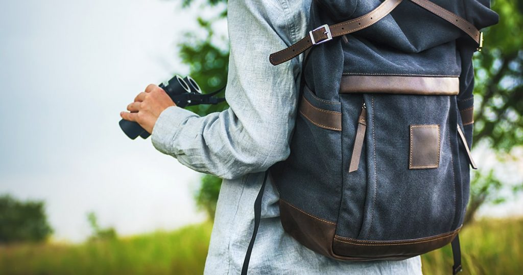 Young adult in shirt with gray backpack holding a binocular