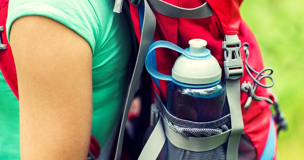 lose up of woman with water bottle in backpack pocket