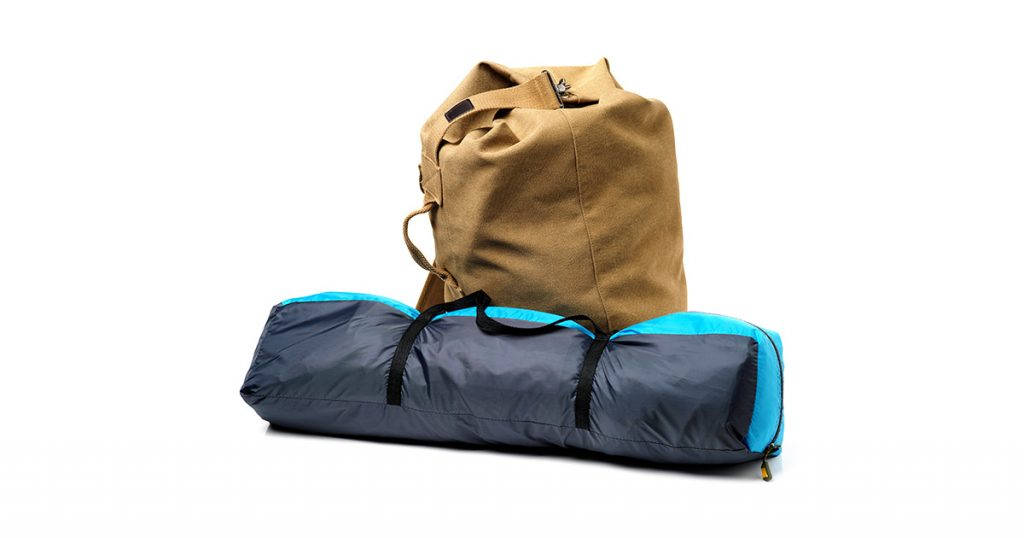 Tourist tent and backpack from fabric of color khaki on white background
