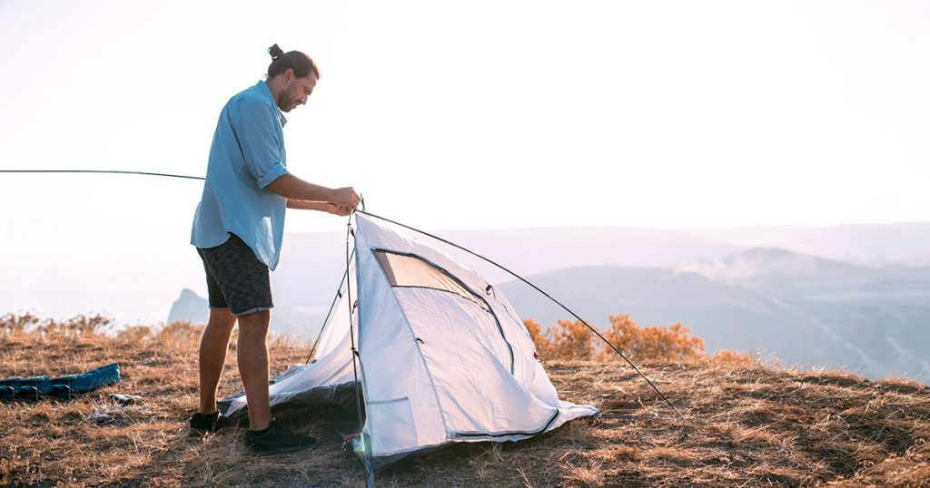 Young male tourist puts a tent in the mountains