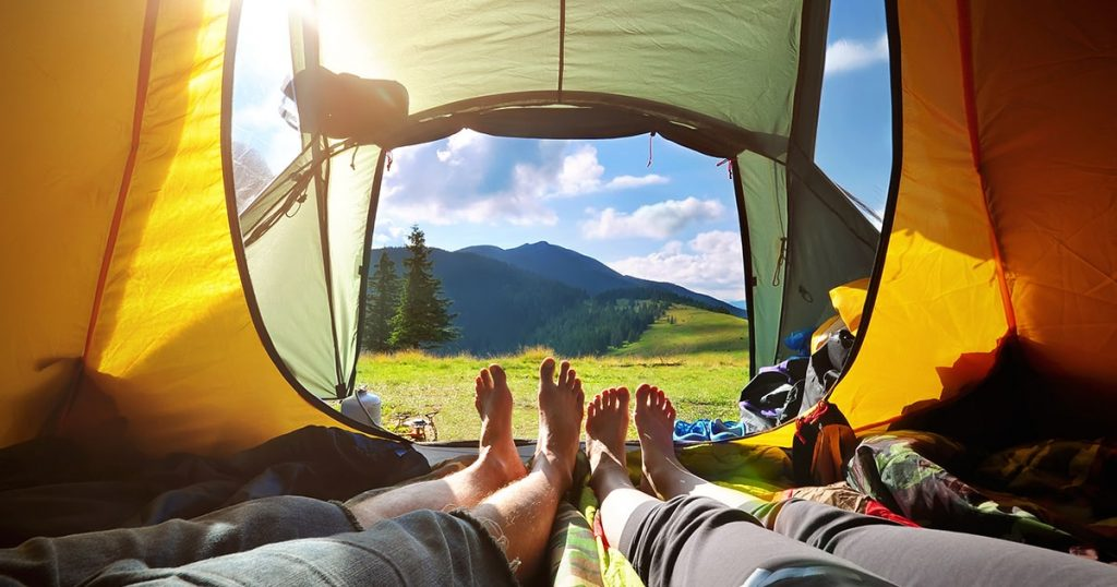 two-people-lying-tent-view-mountains