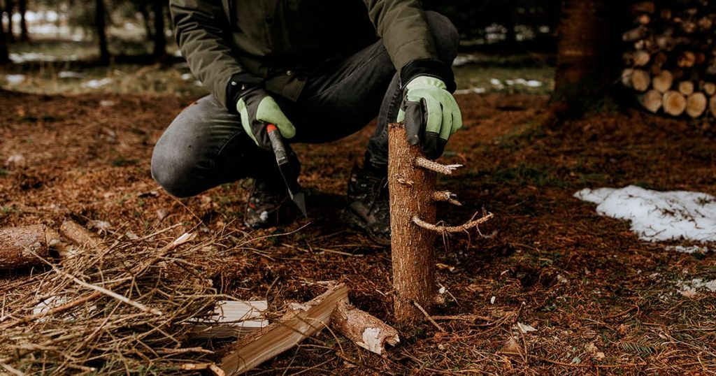 Man strong hands in gloves chop firewood with axe for bonfire