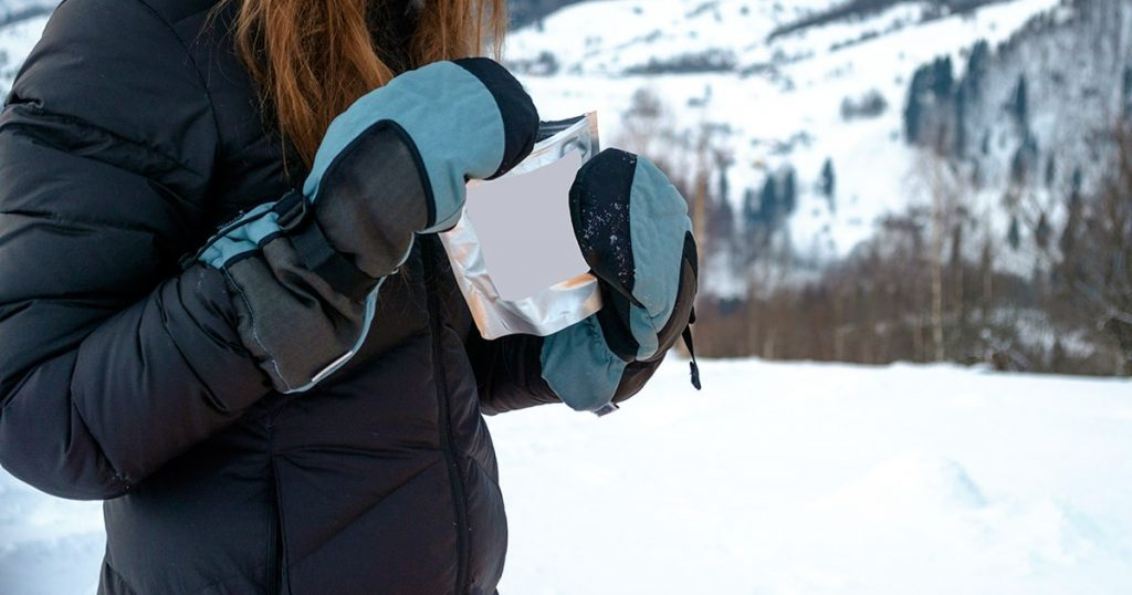woman hiking outdoors with gloves and hat, cold outerwear gear