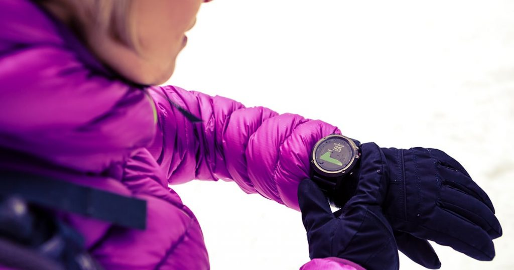 Woman hiker checking the elevation on sports watch